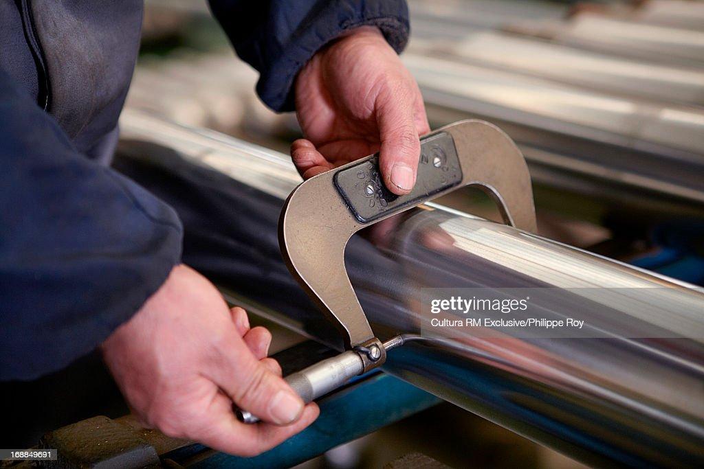 Worker measuring metal rod : Stock Photo