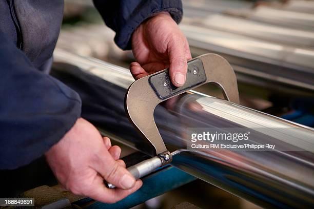 Worker measuring metal rod
