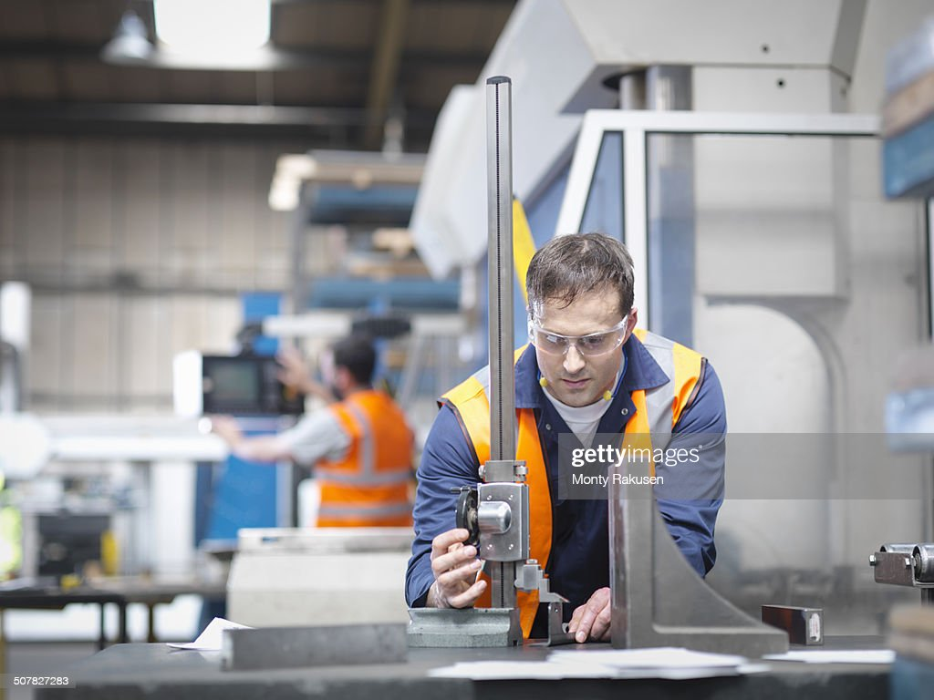 Worker measuring parts in sheet metal factory