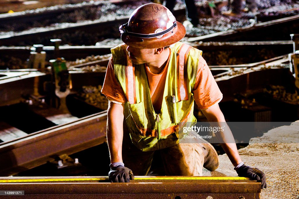 Worker measuring rail with tape : Stock Photo