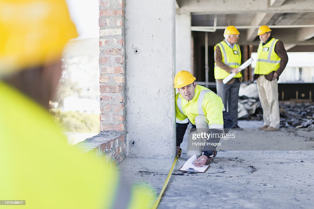 Worker measuring space on site : Stock Photo
