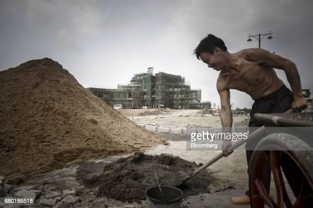 A worker mixes cement near the under construction Beauty Farm International Medical AntiAging Center inside the Hainan Boao Lecheng...