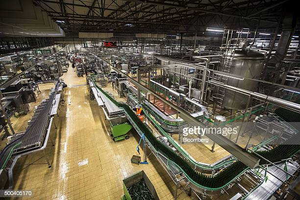 A worker monitors beer bottles as they pass along the automated production line at the Pilsner Urquell brewery operated by SABMiller Plc in Plzen...