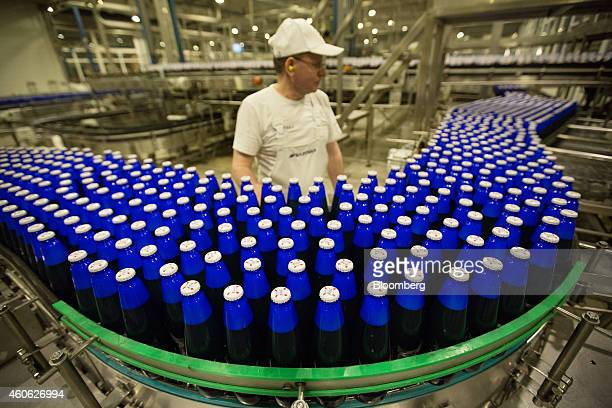 A worker monitors bottles of Kronenbourg 1664 Blanc beer as they move along the production line ahead of labelling at the OAO Baltika brewery...