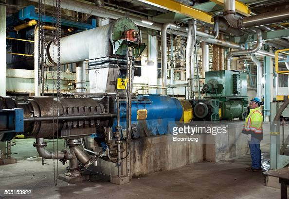 A worker monitors one of the components that moves shaved wood into the pulp and paper machine at the Resolute Forest Products mill in Thunder Bay...
