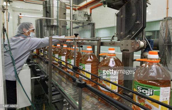 A worker monitors operations as bottles of Saji brand cooking oil move down the production line at the Delima Oil Products Sdn Bhd refinery a...