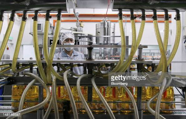 A worker monitors operations on the production line of Saji brand cooking oil at the Delima Oil Products Sdn Bhd refinery a subsidiary of Felda...