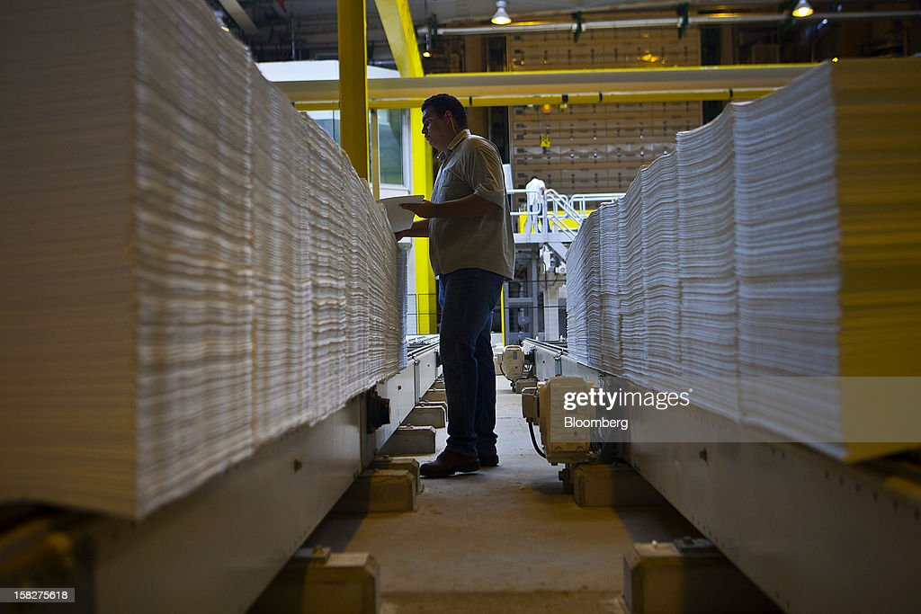 A worker monitors the weight of two ton cellulose sheet packages on the production line at the Eldorado Celulose e Papel S.A processing plant in Tres Lagoas, Brazil, on Wednesday, Dec. 12, 2012. Eldorado Celulose e Papel S.A is finishing construction on a pulp processing plant that is expected to be one of the the world's largest single-line pulp plants when it reaches peak production. Photographer: Dado Galdieri/Bloomberg via Getty Images