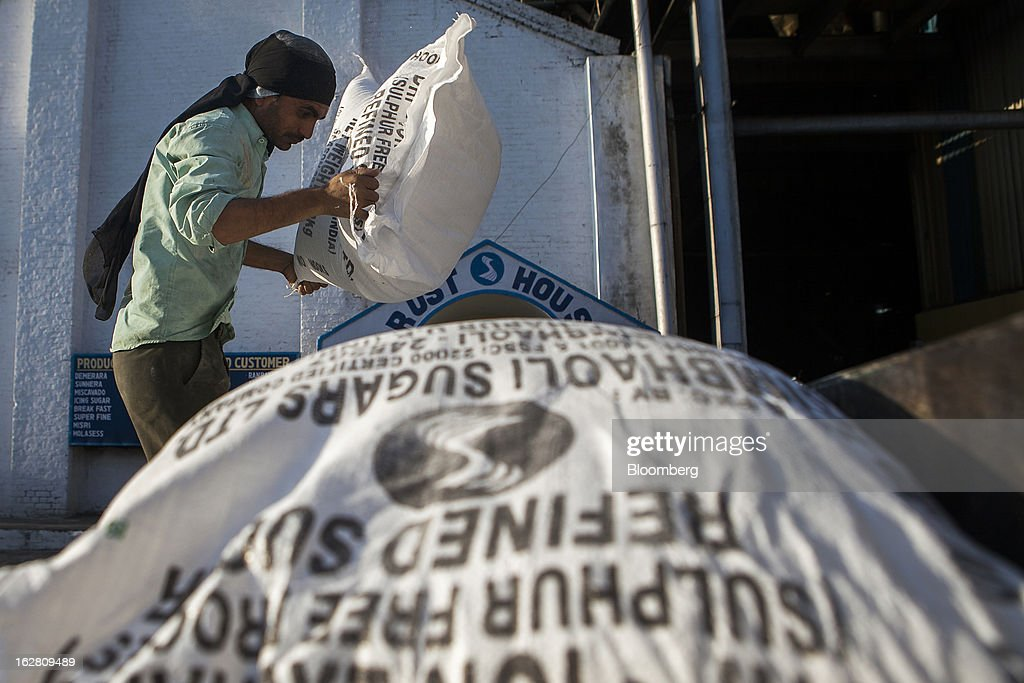 A worker moves a bag of sugar at the Simbhaoli Sugars Ltd. mill in Ghaziabad, Uttar Pradesh, India, on Tuesday, Feb. 26, 2013. India, the world's biggest sugar producer, plans to seek a consensus among various ministries on ending four-decade old state controls on the domestic industry, Food Minister K.V. Thomas said. Photographer: Prashanth Vishwanathan/Bloomberg via Getty Images