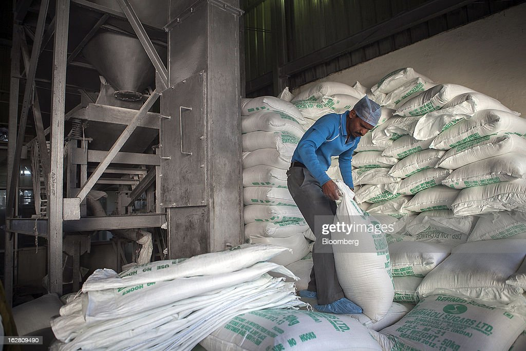 A worker moves a bag of sugar in the packaging unit of the Simbhaoli Sugars Ltd. mill in Ghaziabad, Uttar Pradesh, India, on Tuesday, Feb. 26, 2013. India, the world's biggest sugar producer, plans to seek a consensus among various ministries on ending four-decade old state controls on the domestic industry, Food Minister K.V. Thomas said. Photographer: Prashanth Vishwanathan/Bloomberg via Getty Images