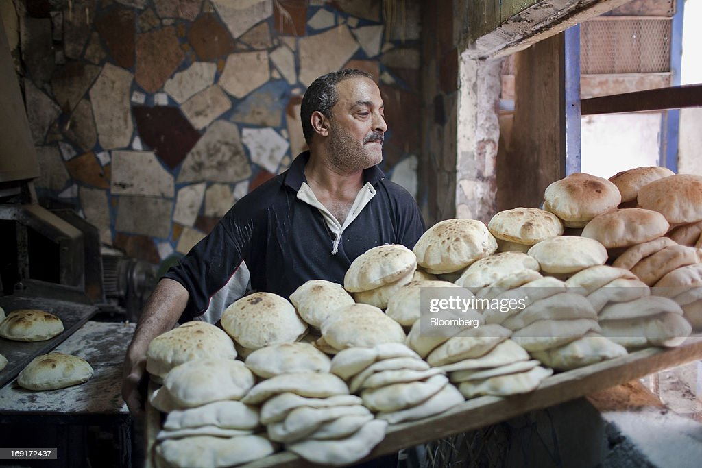 A worker moves a tray of freshly baked bread in a bakery in Cairo, Egypt, on Sunday, May 19, 2013. Egypt will curb wheat imports by 31 percent to 8 million metric tons in 2012-13, still enough to make it the world's biggest buyer, the U.S. Department of Agriculture estimates. Photographer: Shawn Baldwin/Bloomberg via Getty Images