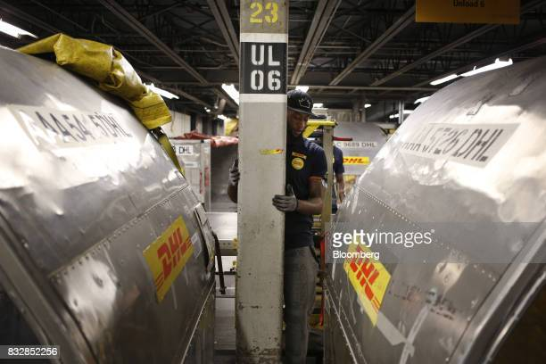 A worker moves between two package containers at the DHL Worldwide Express hub of Cincinnati/Northern Kentucky International Airport in Hebron...