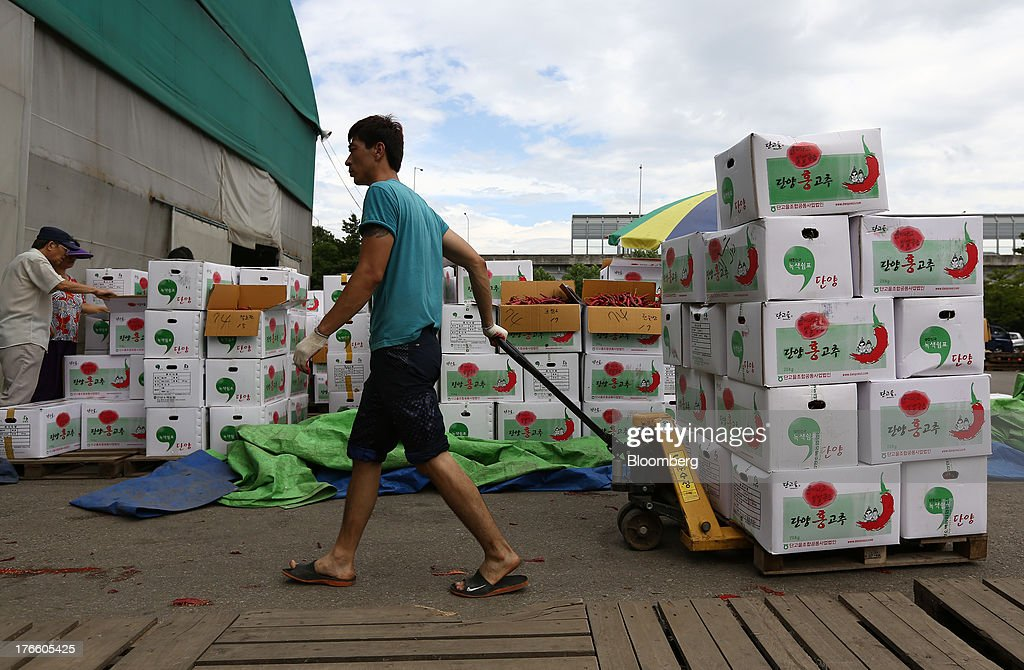 A worker moves boxes of chili peppers at Samsan Agricultural Wholesale Market in Incheon, South Korea, on Friday, Aug. 16, 2013. South Korean producer prices declined 0.9 percent in July from a year earlier after a 1.4 percent drop in June, the central bank said in a statement today. Photographer: SeongJoon Cho/Bloomberg via Getty Images