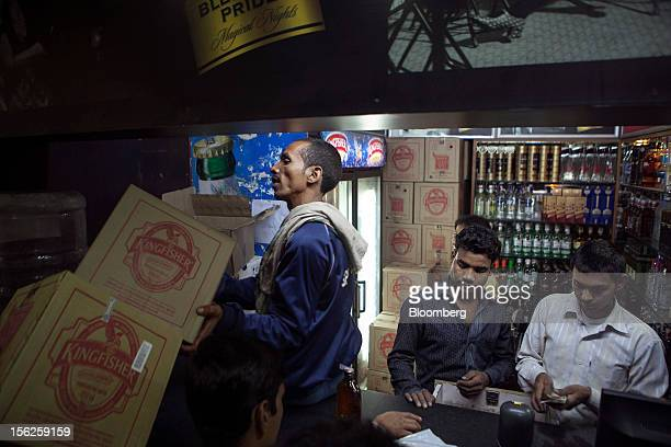 A worker moves cases of United Spirits Ltd's Kingfisher beer at a liquor store in New Delhi India on Monday Nov 12 2012 United Spirits Ltd surged by...
