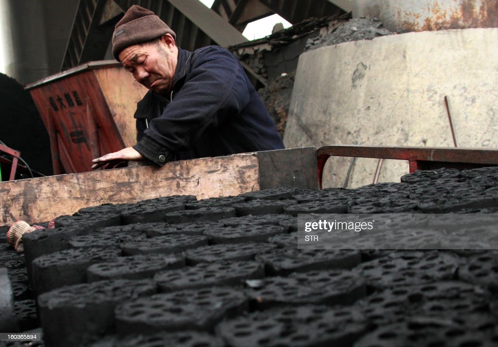 A worker moves coal briquettes onto a pedicab at a coal distribution business in Huaibei , central China's Anhui province on January 30, 2013. Environmental concerns -- particularly over the use of coal -- have been pushed to the top of the agenda after much of the country was covered with a blanket of pollution this past month. The air quality index (AQI) from the Beijing Municipal Environmental Monitoring Centre reached 993 during the worst of the pollution, almost 40 times the World Health Organisation's recommended safe limit. CHINA