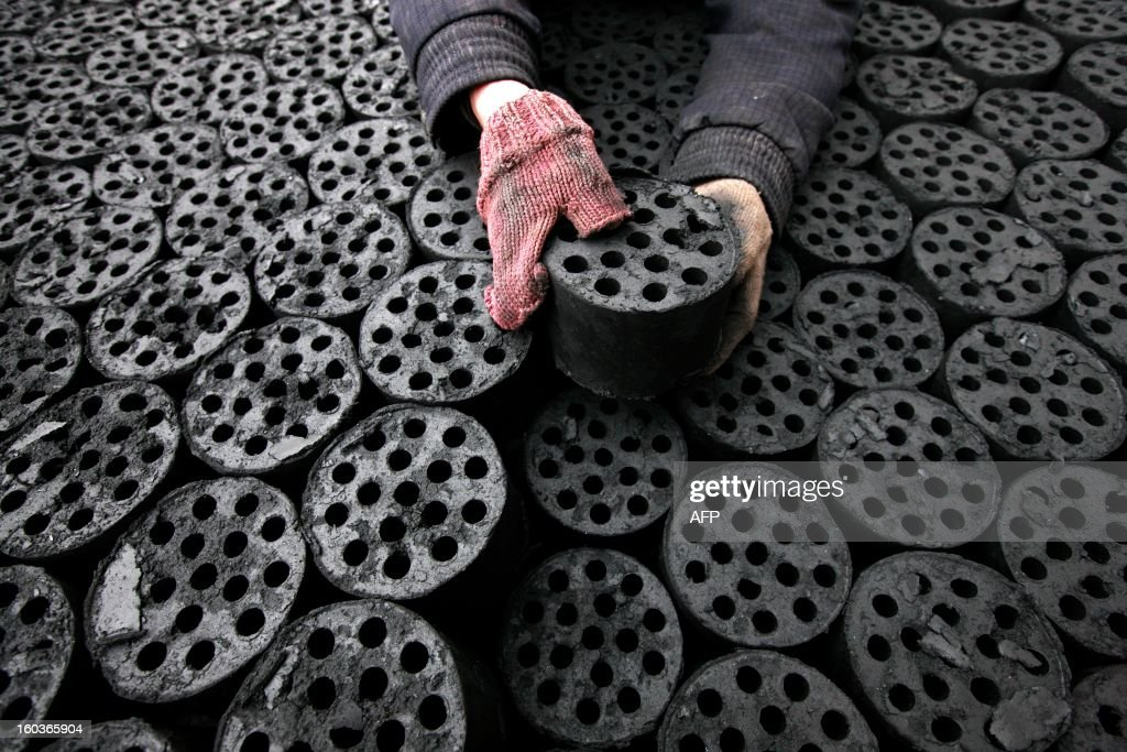 A worker moves coal briquettes onto a pedicab at a coal distribution business in Huaibei, central China's Anhui province on January 30, 2013. Environmental concerns -- particularly over the use of coal -- have been pushed to the top of the agenda after much of the country was covered with a blanket of pollution this past month. The air quality index (AQI) from the Beijing Municipal Environmental Monitoring Centre reached 993 during the worst of the pollution, almost 40 times the World Health Organisation's recommended safe limit. CHINA OUT AFP PHOTO