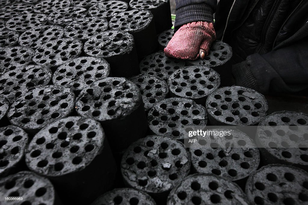 A worker moves coal briquettes onto a pedicab at a coal distribution business in Huaibei, central China's Anhui province on January 30, 2013. Environmental concerns -- particularly over the use of coal -- have been pushed to the top of the agenda after much of the country was covered with a blanket of pollution this past month. The air quality index (AQI) from the Beijing Municipal Environmental Monitoring Centre reached 993 during the worst of the pollution, almost 40 times the World Health Organisation's recommended safe limit. CHINA