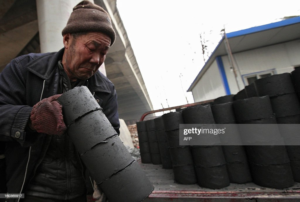 A worker moves coal briquettes onto a pedicabat at a coal distribution business in Huaibei, central China's Anhui province on January 30, 2013. Environmental concerns -- particularly over the use of coal -- have been pushed to the top of the agenda after much of the country was covered with a blanket of pollution this past month. The air quality index (AQI) from the Beijing Municipal Environmental Monitoring Centre reached 993 during the worst of the pollution, almost 40 times the World Health Organisation's recommended safe limit. CHINA OUT AFP PHOTO