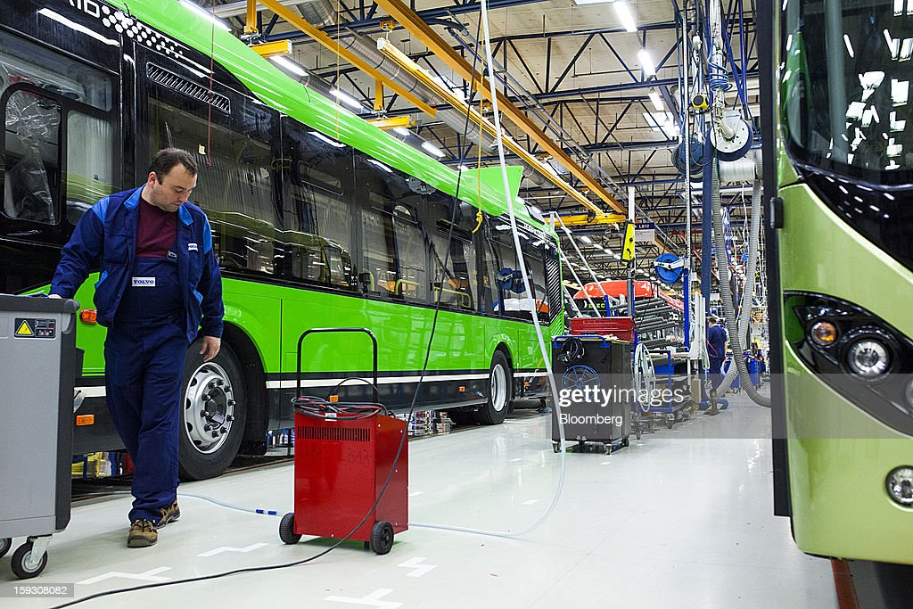 A worker moves equipment past buses during assembly on the production line at Volvo AB's manufacturing plant in Wroclaw, Poland, on Friday, Jan. 11, 2013. Volvo plans to end bus making in Saeffle by June 2013, and will consolidate the business in Europe to its main plant in Wroclaw, Poland, the Gothenburg, Sweden-based company said. Photographer: Bartek Sadowski/Bloomberg via Getty Images