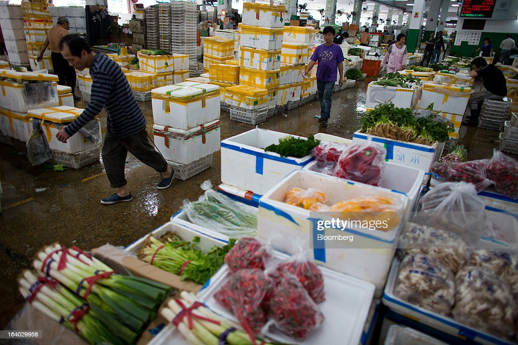 A worker moves foam boxes of produce past vegetables in open boxes at the Cheung Sha Wan Wholesale Vegetable Market in Hong Kong, China, on Tuesday, March 19, 2013. Hong Kong's economy expanded 1.4 percent in 2012 and Financial Secretary John Tsang is projecting growth of 1.5 percent to 3.5 percent this year. Photographer: Lam Yik Fei/Bloomberg via Getty Images.