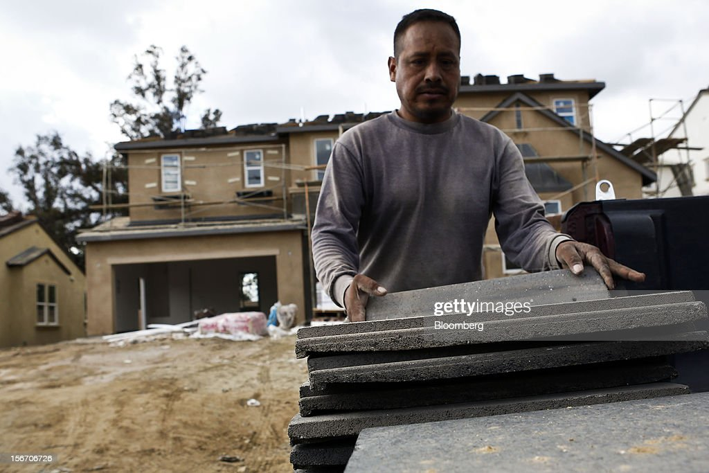 A worker moves roofing tiles during the construction of a new home at the Van Daele Estates at Etiwanda development in Rancho Cucamonga, California, U.S., on Sunday, Nov. 18, 2012. The U.S. Census Bureau is scheduled to release housing starts figures on Nov. 20. Photographer: Patrick T. Fallon/Bloomberg via Getty Images
