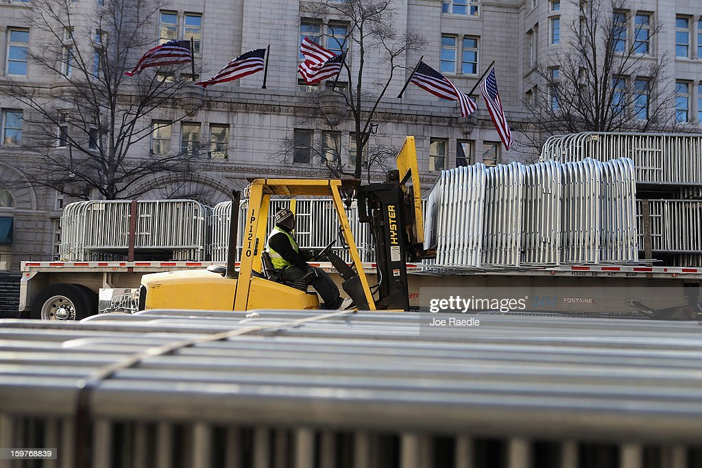 A worker moves security fences into position along Pennsylvania Ave as preparations continue for the Inauguration Parade on January 20, 2013 in Washington, DC. The US capital is preparing for the second inauguration of US President Barack Obama, which will take place on January 21.