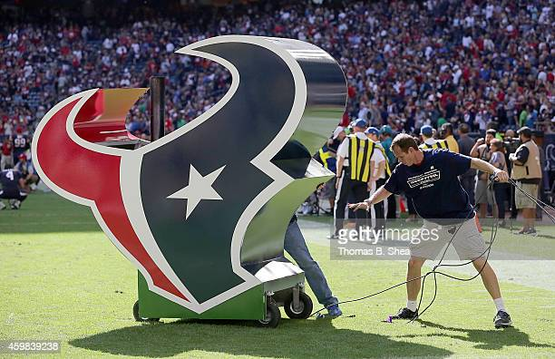A worker moves the Houston Texans logo before the Houston Texans played the Tennessee Titans in a NFL game on November 30 2014 at NRG Stadium in...