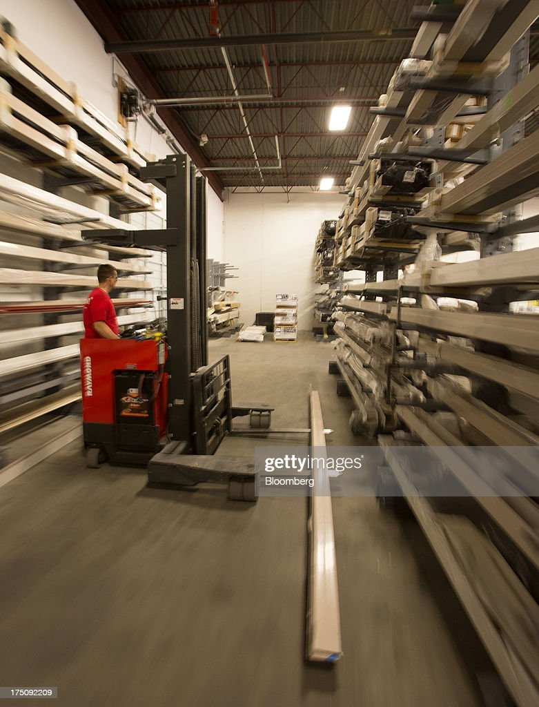 A worker moves window frame extrusions in a warehouse at the Milgard Windows & Doors' manufacturing facility in Tacoma, Washington, U.S., on Wednesday, July 24, 2013. The U.S. Census Bureau is scheduled to release monthly factory orders figures on Aug. 2. Photographer: Tim Rue/Bloomberg via Getty Images