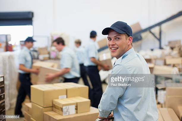 Worker moving boxes on hand cart in shipping area