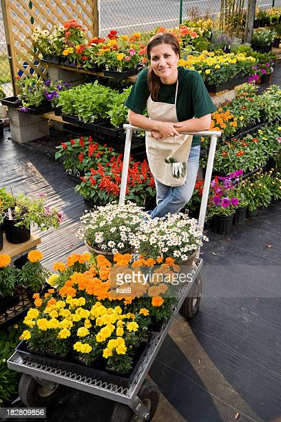 Worker moving merchandise in retail plant store