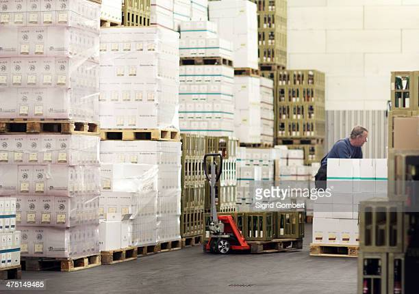 Worker moving packaged boxes of wine