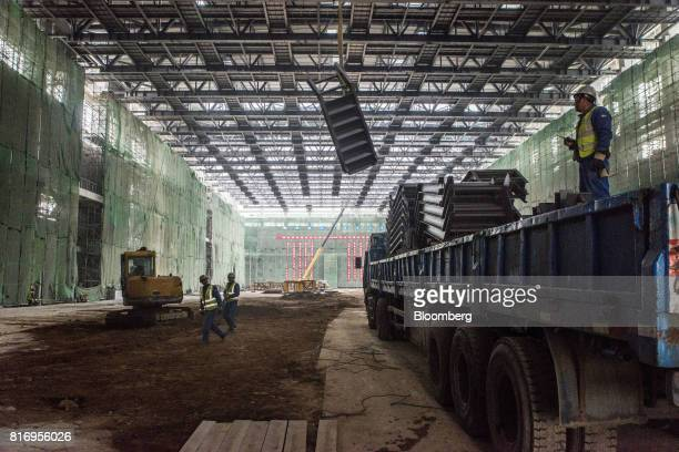 A worker observes a hoist from the back of a truck at a film stage construction site inside the Dalian Wanda Group Co Oriental Movie Metropolis...