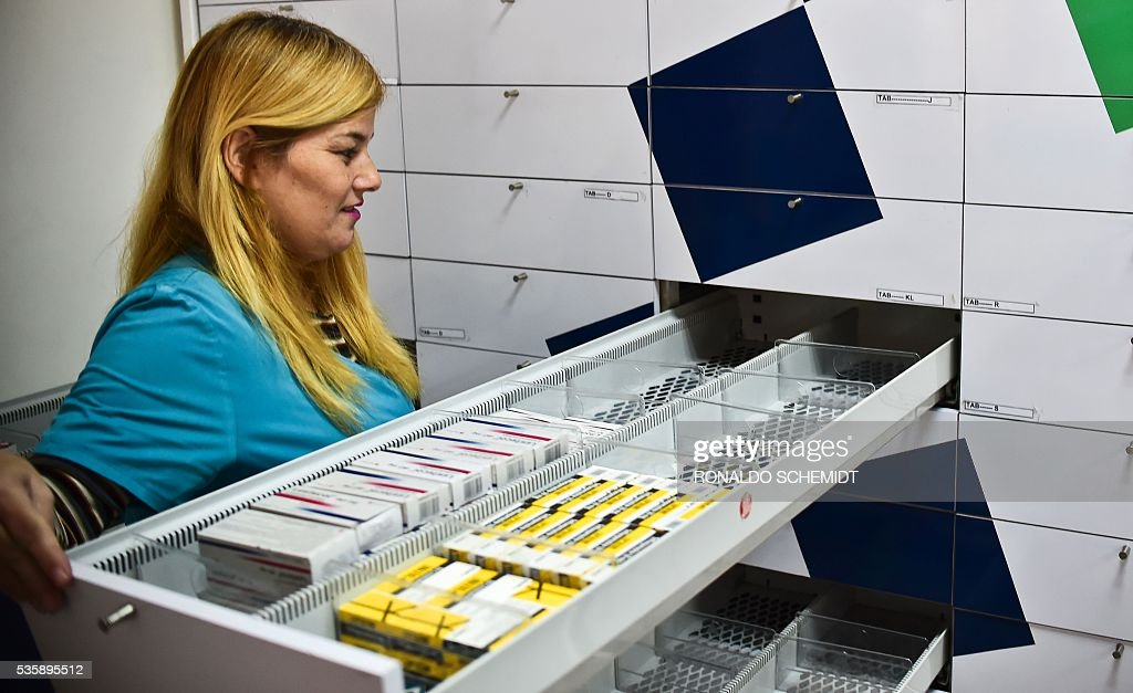 A worker of a pharmacy opens a half empty empty drewer in Caracas on May 30, 2016. The shortage of medicines in Venezuela exceeds 85%, revealed the president of the harmaceutical federation of Venezuela, Freddy Ceballos. / AFP / RONALDO