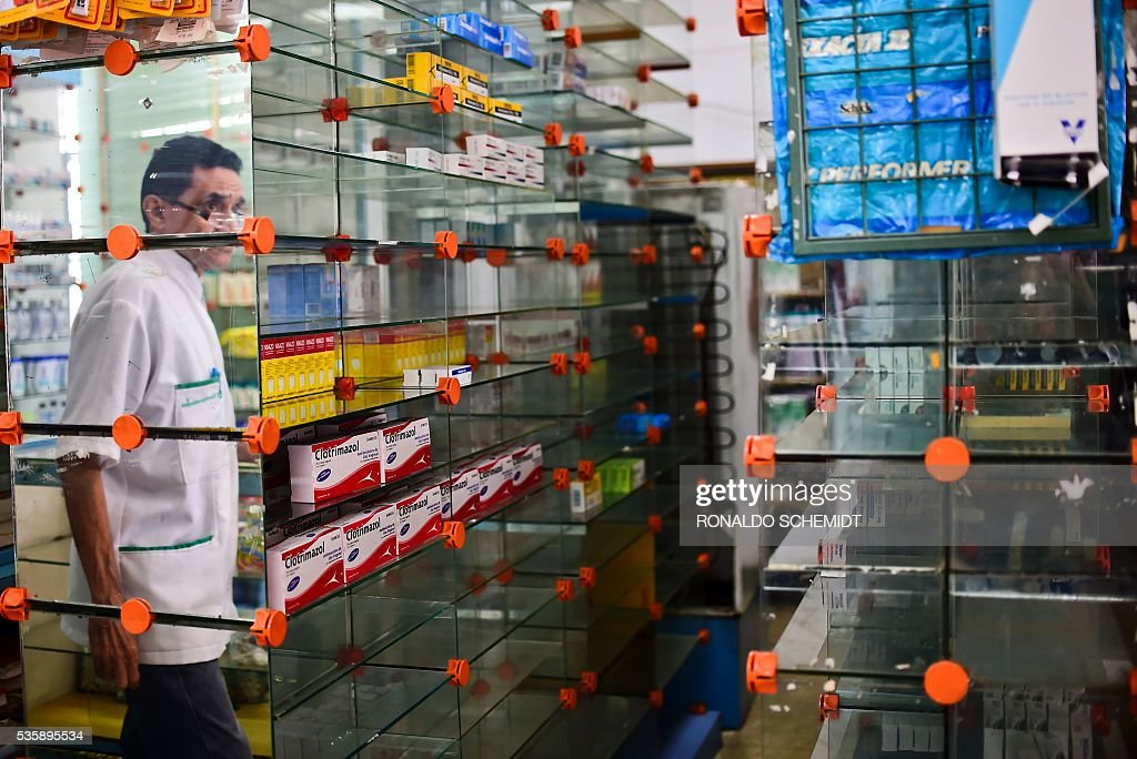 A worker of an empty pharmacy is pictured in Caracas on May 30, 2016. The shortage of medicines in Venezuela exceeds 85%, revealed the president of the harmaceutical federation of Venezuela, Freddy Ceballos. / AFP / RONALDO