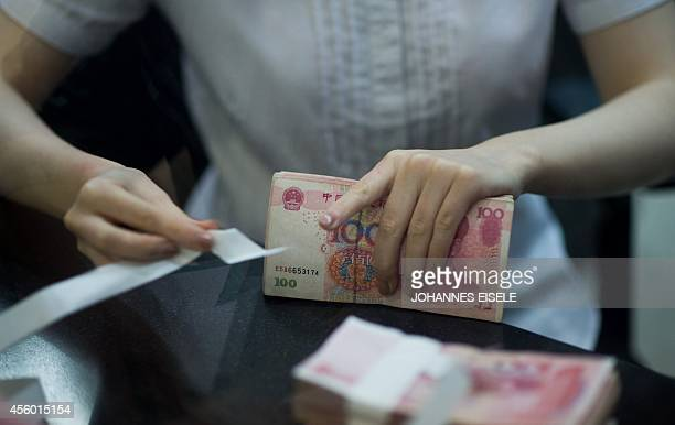 A worker of an Industrial and Commercial Bank of China Ltd branch counts money as she serves a customer in the China Pilot Free Trade zone during a...