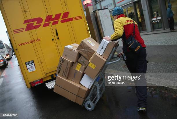 A worker of DHL delivers packages during the busy Christmas season on December 9 2013 in Berlin Germany According to a recent study people in Germany...