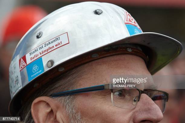 A worker of German heavy industry giant ThyssenKrupp wears a hard hat with a sticker reading ' Steel is future that is what we are fighting for' on...