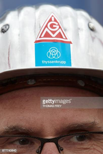 A worker of German heavy industry giant ThyssenKrupp wears a hard hat with a sticker of the union IG Metal and ThyssenKrupp on November 23 2017 in...
