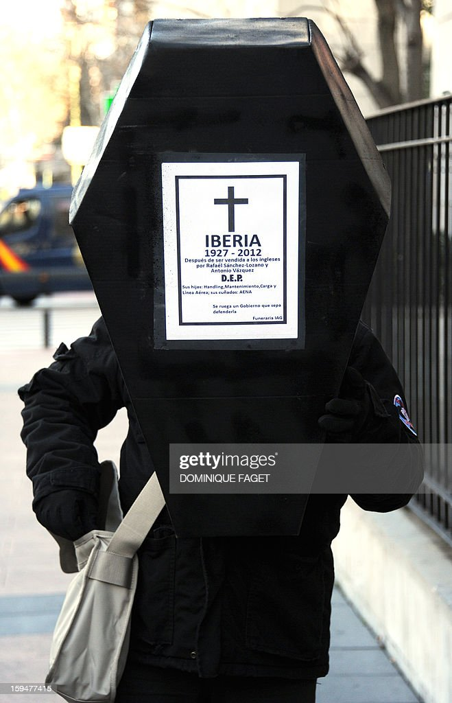 A worker of Iberia holds a mock coffin during a demonstration outside the Spanish airline Iberia headquarters in Madrid on January 14, 2013. Around 100 employees of Iberia gathered today at the company's headquarters to protest against a restructuring plan for the company and its merger with British Airways which imply about 4,000 jobs lay-offs.