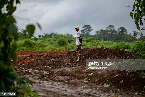 A worker of International Committee of the Red Cross is responsible for mowing grass with a reaping hook in the construction area during the...