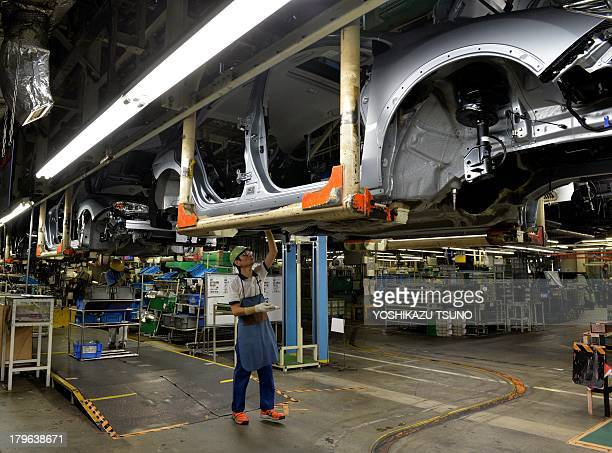 A worker of Japan's auto maker Fuji Heavy Industries known as Subaru brand assembles auto parts to the vehicle at the company's Gunma Yajima Plant at...