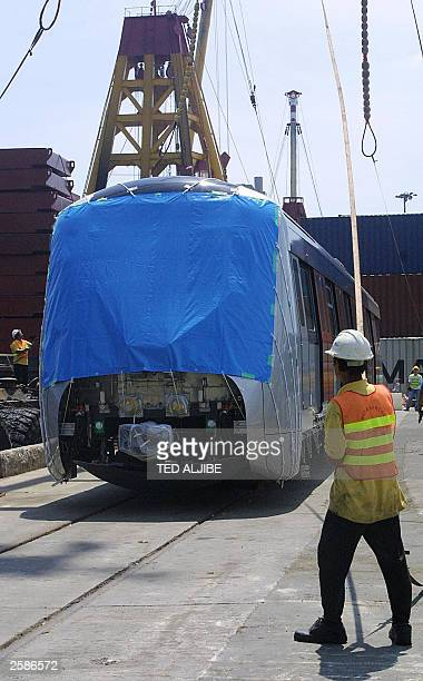 A worker of Kowloon Canton Railway holds a rope as one of the new train cars is unloaded at the company''s freight yard in Hong Kong 26 September...