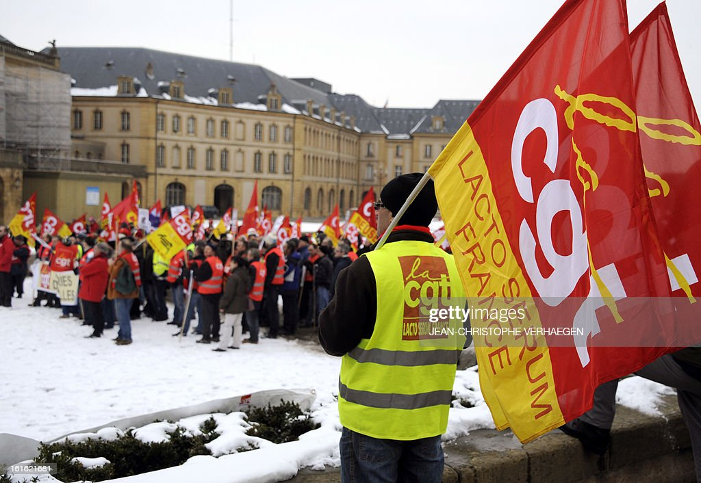 A worker of Lacto Serum France (R) holds a flag of French CGT trade union on February 13, 2013 in Metz, eastern France, as he takes part in a demonstration with about 700 protesters to claim for the safeguard of the local industry in the French eastern region of Lorraine.