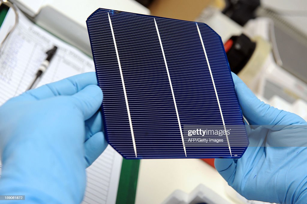 A worker of MPO Energy holds a photovoltaic cells made at a MPO plant in Averton, western France, on January 7, 2013.