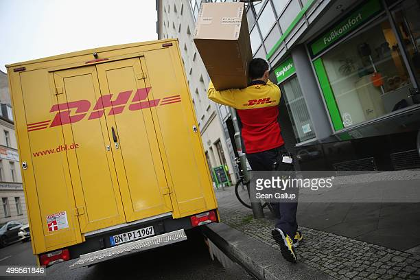 A worker of parcel deliverer DHL which is a subsidiary of Deutsche Post delivers packages on December 2 2015 in Berlin Germany As the Christmas...