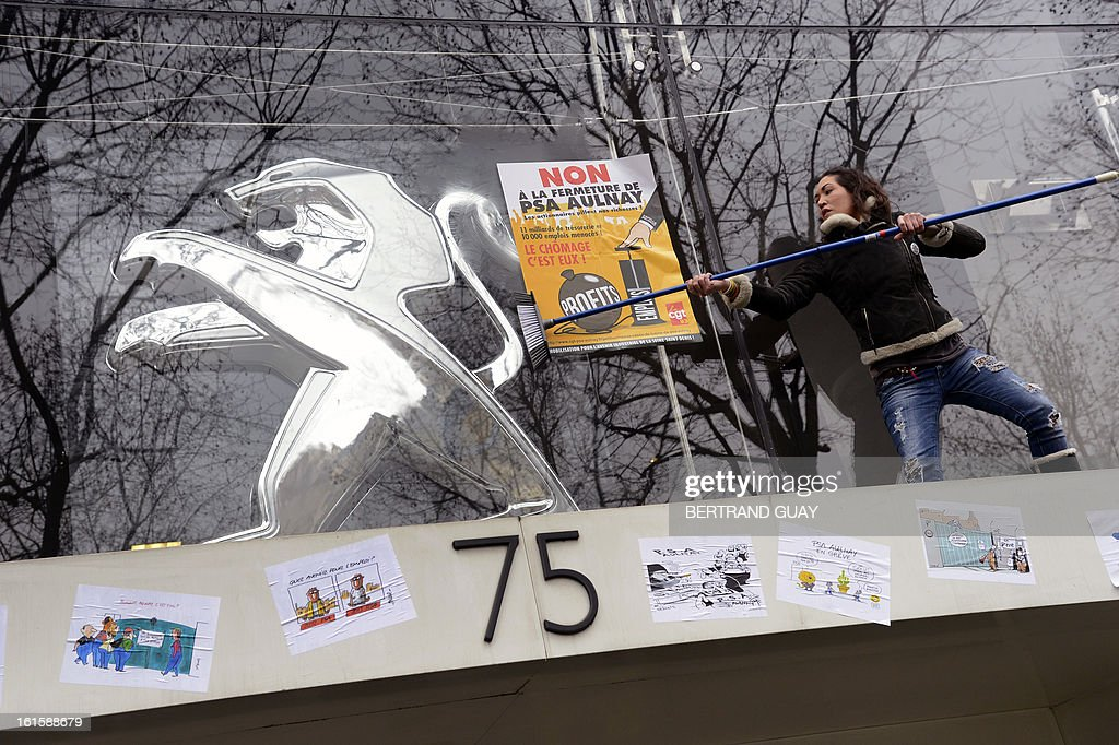 A worker of PSA Peugeot Citroen car maker sets placards on the facade of the group's headquarters, on February 12, 2013 in Paris, during a demonstration to protest against the group's restructuration plan which involves more than 11.200 job cuts in France, at the time of a negociation meeting on the social support measures accompanying the plan. AFP PHOTO BERTRAND GUAY