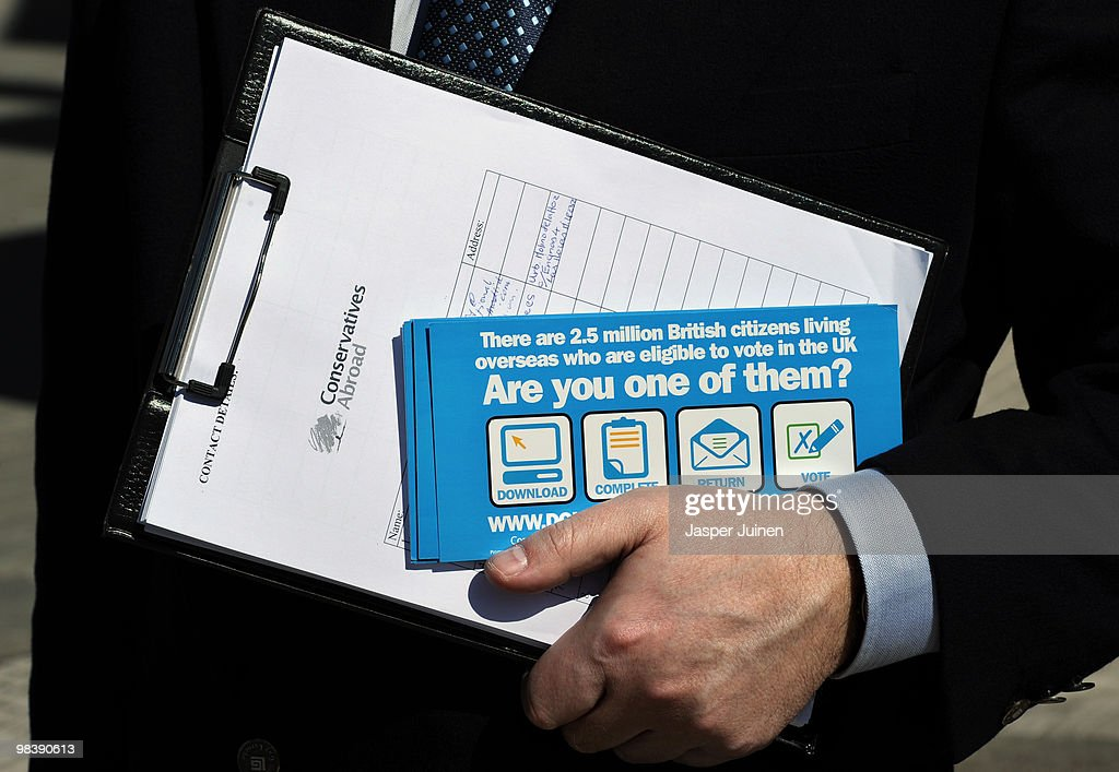 A worker of the 'Conservatives Abroad' organisation holds registration papers and pamflets promoting the Conservative Party as he waits to register...