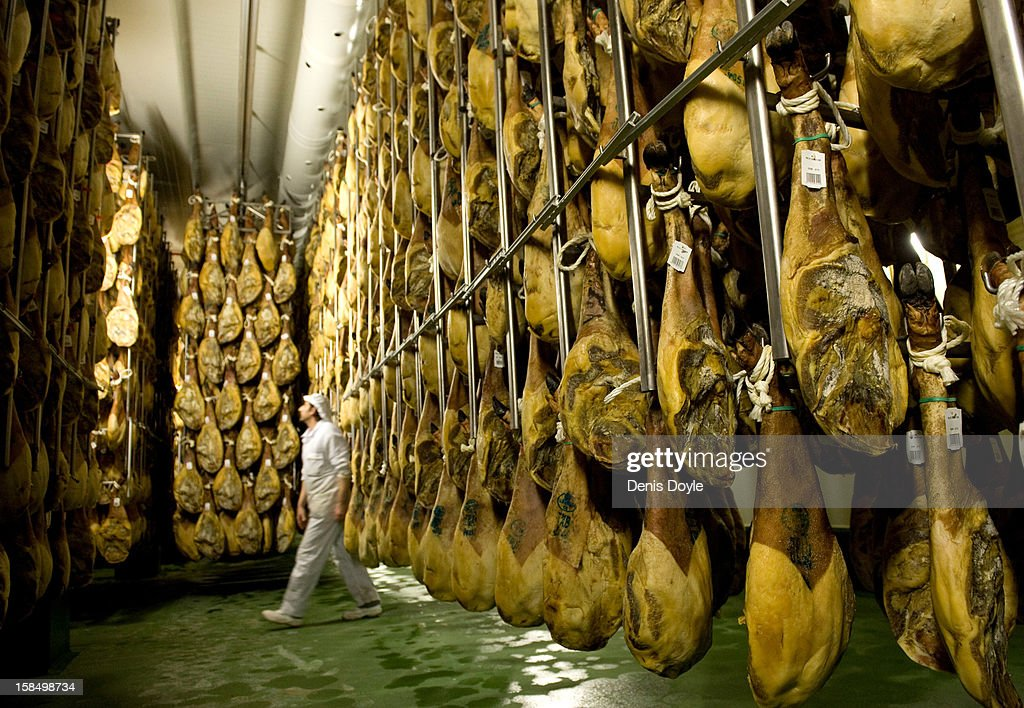 A worker of the Estrella de Castilla factory walks past rown of dry-cured Jamon Iberico de bellota (acorns) in the in the town of Guijuelo on December 14, 2012 near Salamanca, Spain. Dry-cured Iberian ham or Jamon Iberico de Bellota is a favourite amongst Spaniards and producers are hoping for improved sales over the busy christmas period. The jamon Iberico de Bellota are usually dry-cured for up to three years after the pigs have been few on a diet of acorns in the last three months of their lives.