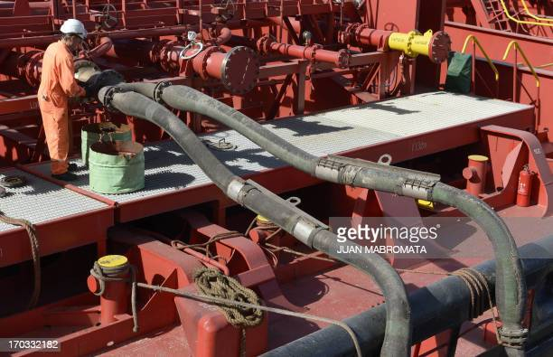 A worker of the Norient Saturn vessel checks the pipes while filling up the tank with soy bean oil at the General San Martin port on the Parana river...