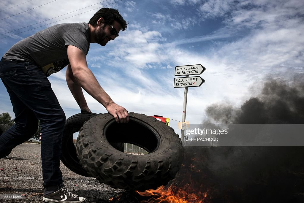 A worker of the Tricastin nuclear power plant burns tyres and set up a barricade at the entrance of the site on May 26, 2016 in Saint-Paul-Trois-Chateaux, during a protest against controversial labour market reforms that has already severely disrupted fuel supplies. With two weeks until France hosts the Euro 2016 football championships, the country has been paralysed by a series of transport strikes and fuel shortages that has heaped pressure on the deeply unpopular Socialist government. / AFP / JEFF